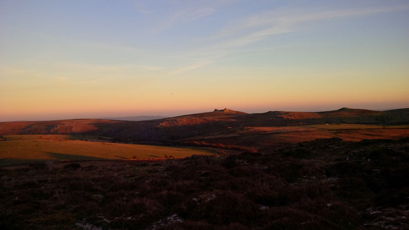 The setting sun casts warm colours over the landscape of Dartmoor