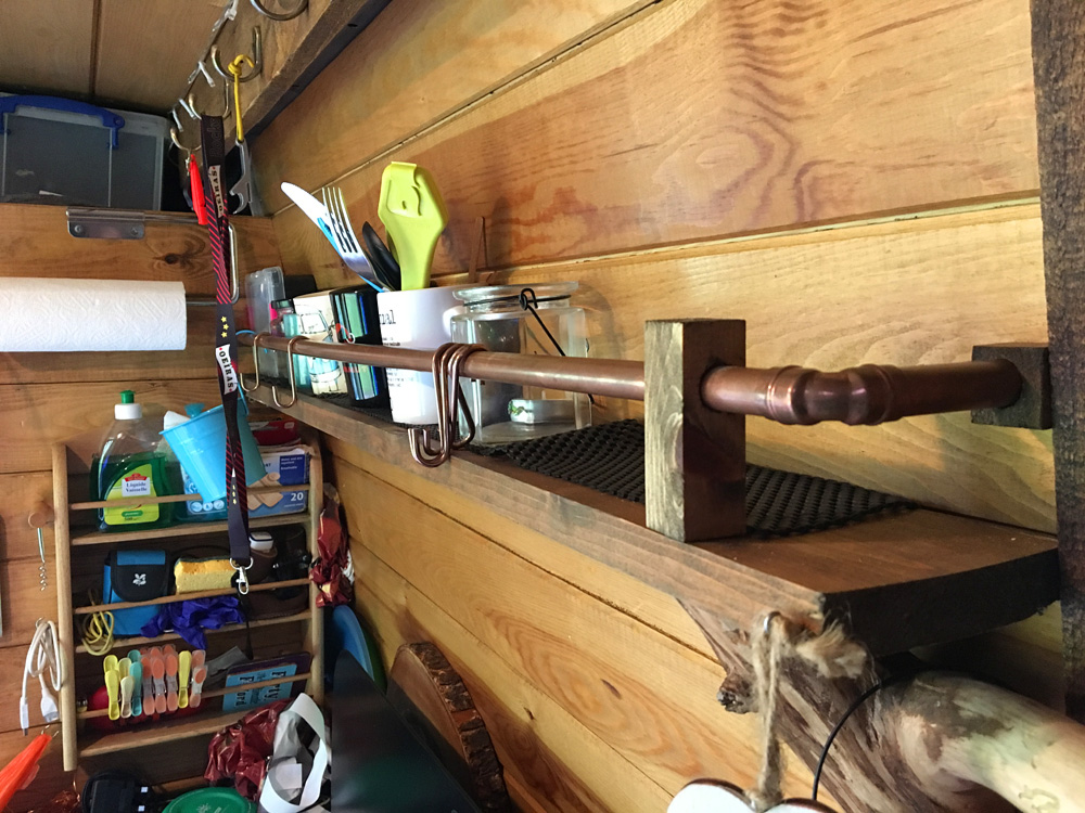 The kitchen shelf with copper pipe retaining rail